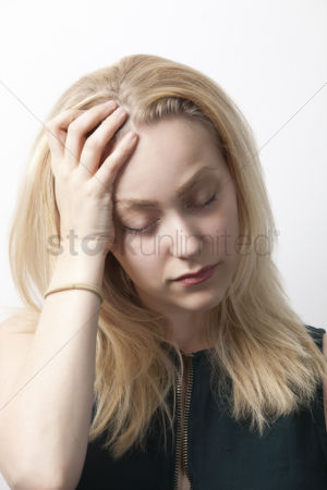 Pain : Young woman suffering from headache against white background