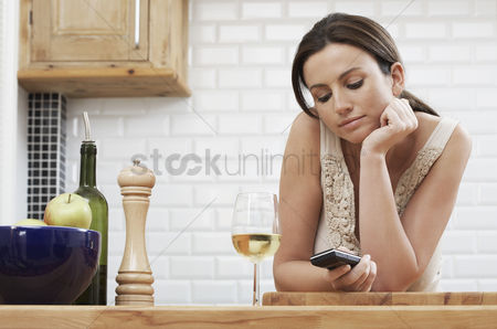 Wine bottle : Young woman text messaging leaning on kitchen counter