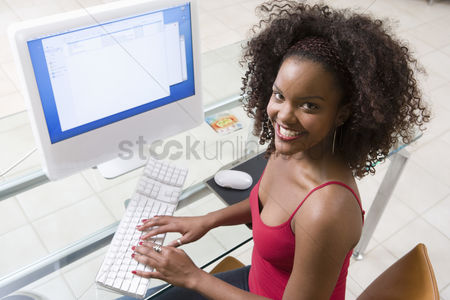 Posed : Young woman using desktop computer