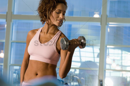 Fitness : Young woman using dumbbell in gymnasium