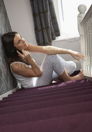 Steps : Young woman using telephone sitting on stairs in home