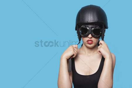 20 24 years : Young woman wearing nostalgic helmet and goggles against blue background