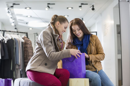 Shopping : Young woman with friend looking into shopping bag at store