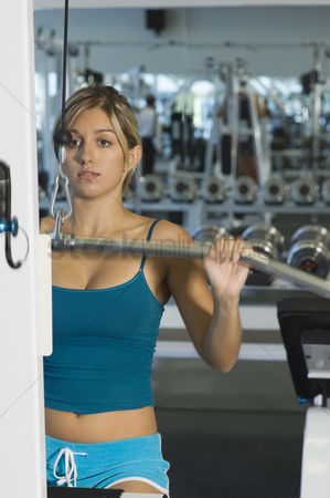 Workout : Young woman working out on weightlifting machine