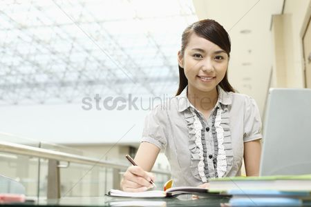 Accessibility : Young woman writing  smiling