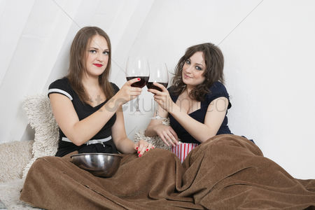 Toasting : Young women toasting with wine glasses in bed