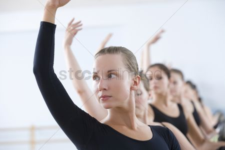 Dance : Young women with arms raised at the barre